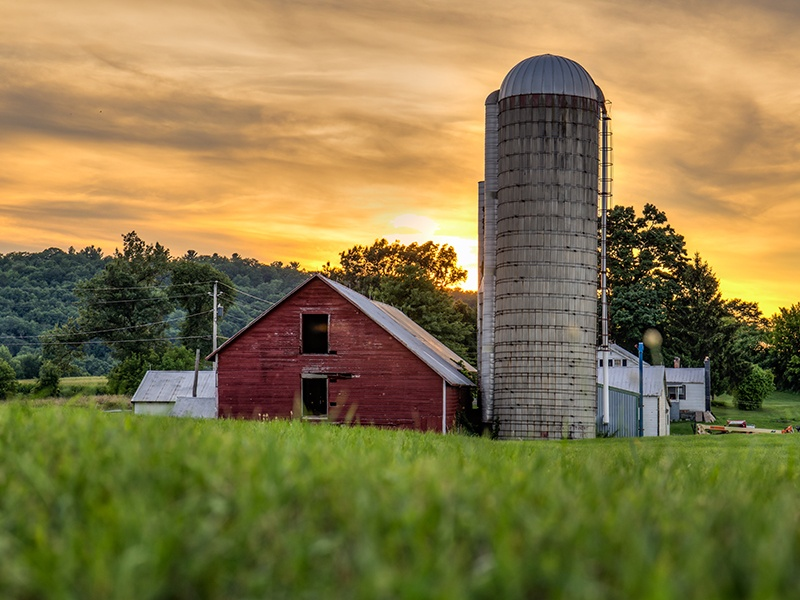 Red barn and farmstead with sunset